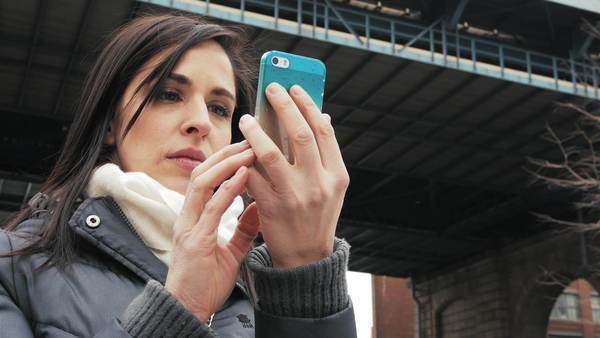 Beautiful girl on her mobile phone underneath a Bridge Royalty-free stock video