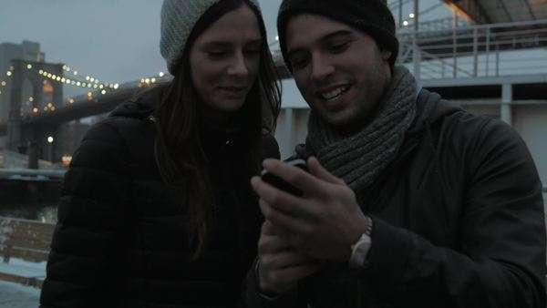Young attractive couple looking at photo they took on smartphone with Brooklyn Bridge in background Royalty-free stock video