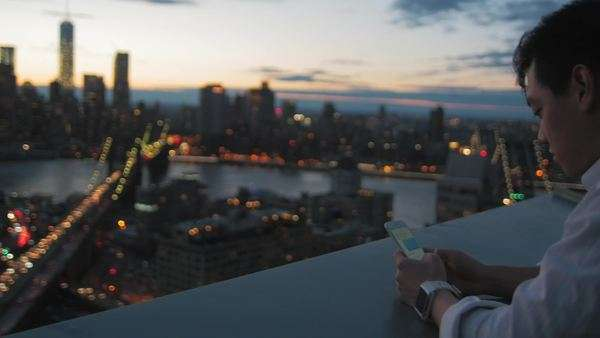 Pan of young man texting on his smartphone and Manhattan, New York at sunset Royalty-free stock video