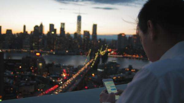 Young man texting on his iPhone with Manhattan skyline in background Royalty-free stock video