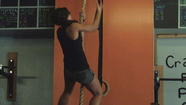 Personal trainer coaching female athlete to climb rope Royalty-free stock video