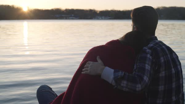 Medium shot of a couple relaxing at a lake shore Royalty-free stock video