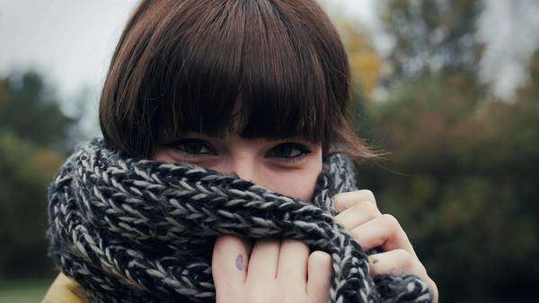 Beautiful young woman snuggles into her scarf and then smiles at camera Royalty-free stock video