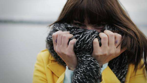 Young woman plays peek-a-boo with her scarf Royalty-free stock video