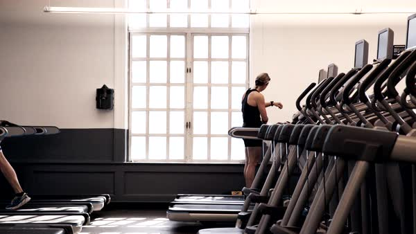 Medium shot of a woman standing on a treadmill in a gym Royalty-free stock video