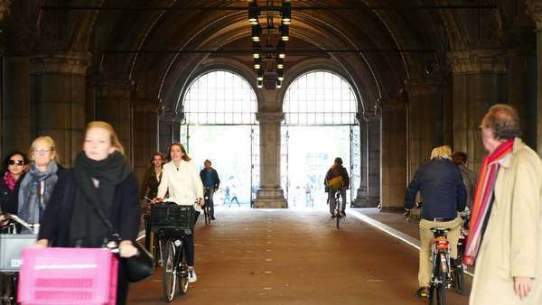Time lapse Zoom - Bicyclists in the Rijksmuseum Building Tunnel - Amsterdam Netherlands Royalty-free stock video