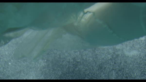 Slow motion shot of woman in white gown swimming underwater Royalty-free stock video