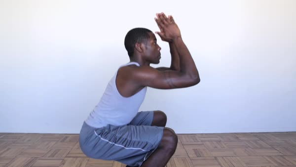 Hand-held shot of a young man doing squats in studio Royalty-free stock video