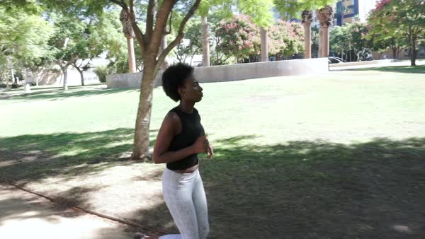 Hand-held shot of a young woman running in park Royalty-free stock video