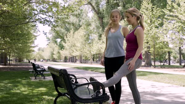 Fit Young Women Stretch Their Legs On A Bench, And Warm Up Before Workout Routine In Park Royalty-free stock video
