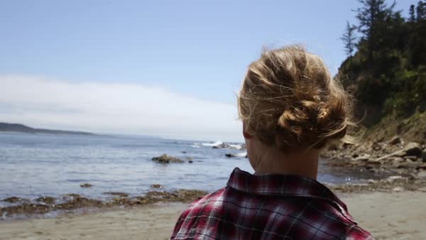 Closeup Of Young Woman Walking Along The Beach In The Pacific Northwest, Her Friend Walks Ahead Of Her Royalty-free stock video