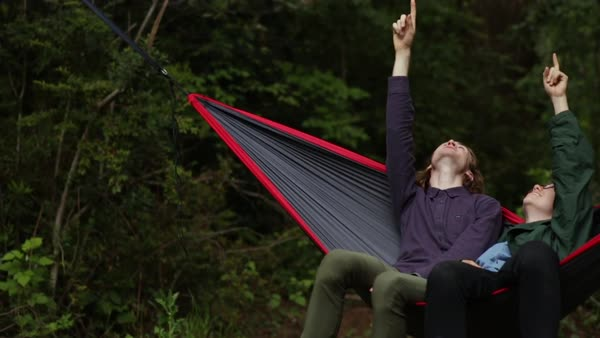 Friends Lean Back In Hammock, Look Above, They Point To Something At The Same Time, Laugh (Slow Motion) Royalty-free stock video