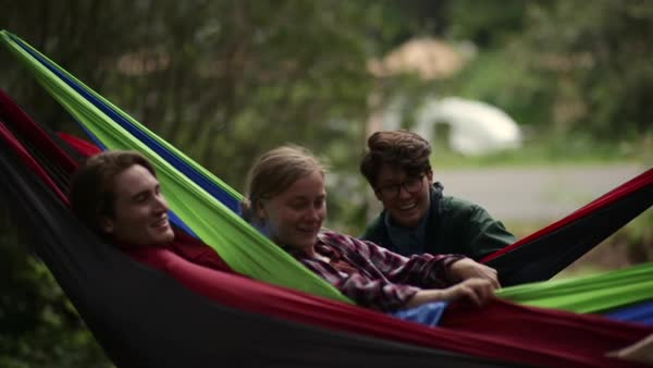 Group Of Friends Enjoy Hanging Out In Hammocks At Campground, Man Hides Inside His, Friends Laugh Royalty-free stock video