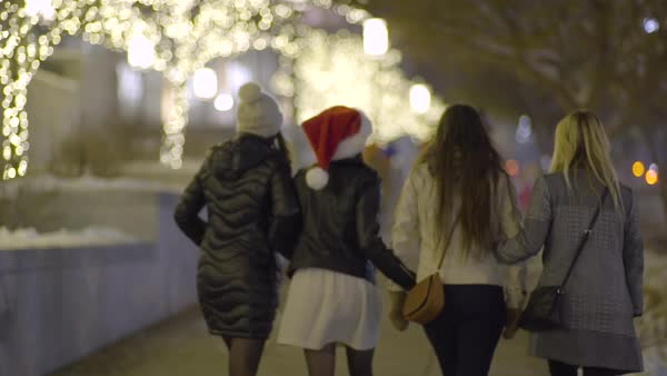 Group of fun girls dressed up for holiday party walk down city sidewalk at night, enjoying light display Royalty-free stock video