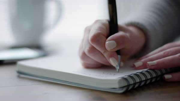 Close-up of woman writing in notebook, phone and coffee next to her  Royalty-free stock video