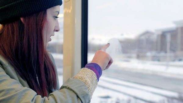Happy teen rides train, she fogs up her window, and draws a smiley face with her finger Royalty-free stock video