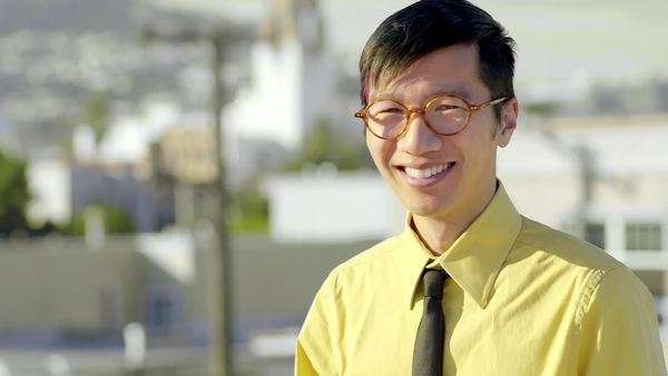 Man in business casual attire smiles and looks out at view of San Fancisco from rooftop Royalty-free stock video