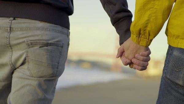 Gay couple hold hands and walk down beach toward Golden Gate Bridge (slow motion) Royalty-free stock video