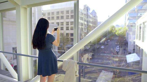 Teen takes a photo of city below her, from a skybridge (lens flare) Royalty-free stock video