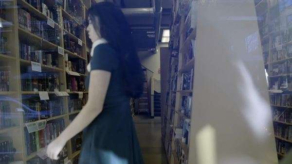 Teen walks in book store aisle, finds a book on the shelf Royalty-free stock video