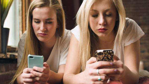 Two Fun Teenage Girls Play With Their Smart Phones And Take A Photo Together Royalty-free stock video