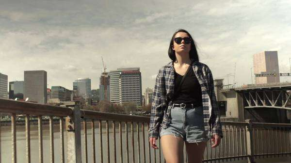 Teen explores waterfront park, city behind her. slow motion Royalty-free stock video