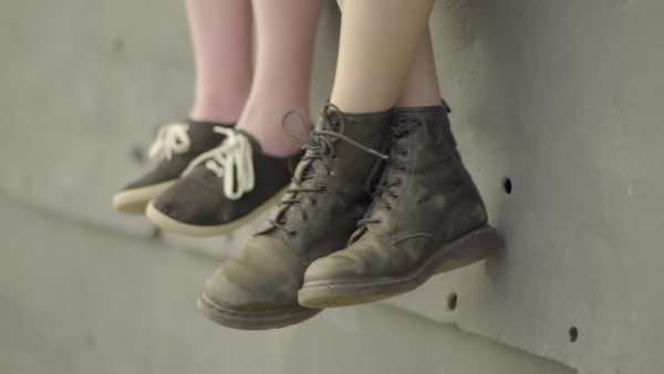 Close-up of two teen's feet hanging over the edge of a wall, hanging out. slow motion Royalty-free stock video