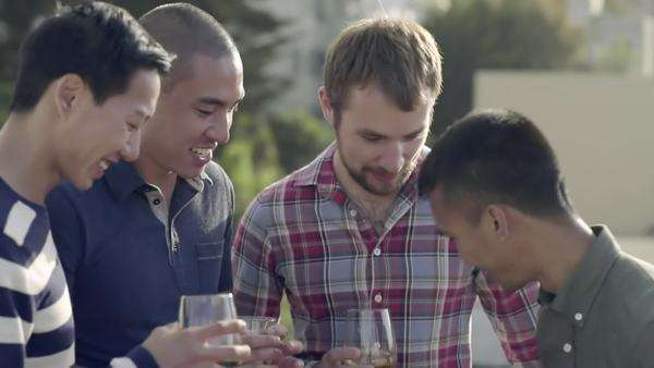 Gay friends enjoy happy hour on a rooftop in San Francisco, they look through phone pics and man takes a group photo Royalty-free stock video