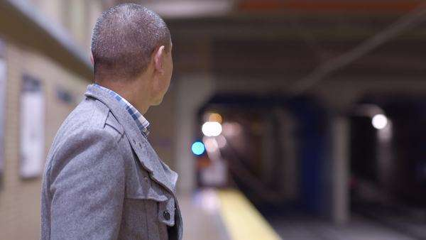 Man looks on as train approaches in subway station Royalty-free stock video