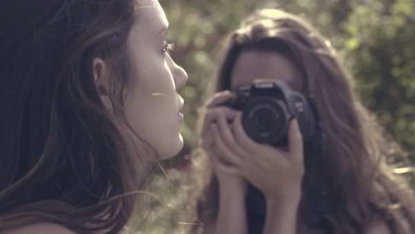 Beautiful photographer takes photos of young woman in nature, slow motion Royalty-free stock video