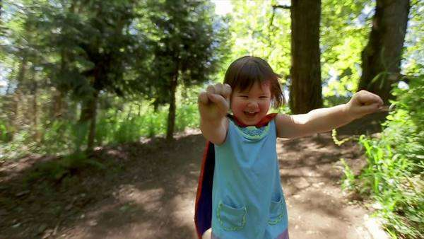 Closeup of little girl with fists out, pretending to fly in her superhero cape (slow motion) Royalty-free stock video