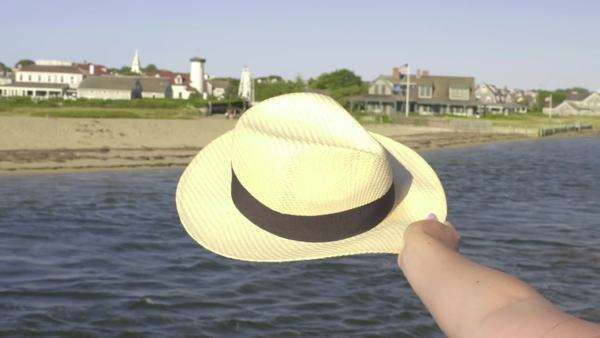 Woman waves her sun hat in the sea breeze, from moving boat, at Nantucket Island Royalty-free stock video