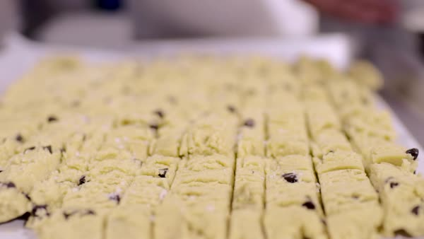 Woman sprinkles sugar over sliced cookie dough on cookie sheet, preparing it for cookie dough ice cream Royalty-free stock video