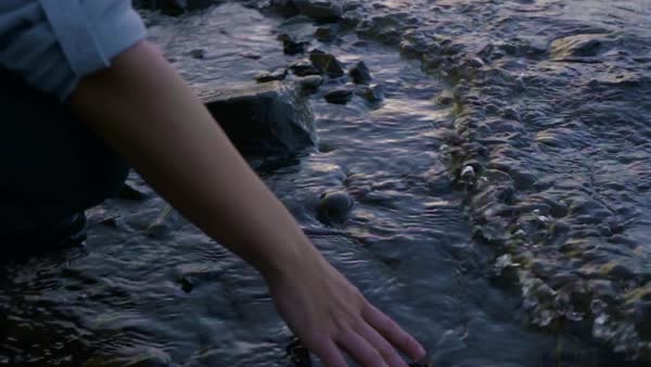 Closeup of woman's hand playing in water on rocky shoreline at sunset Royalty-free stock video