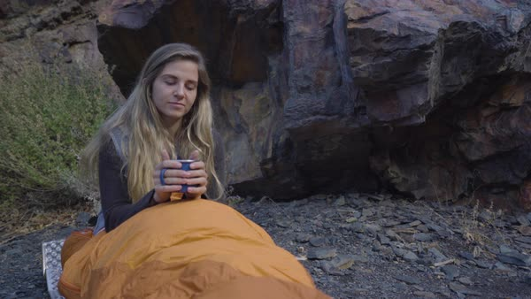 Closeup Of Adventurous Young Woman On Solo Backpacking Trip, She Enjoys Her Morning Coffee From Her Sleeping Bag Royalty-free stock video