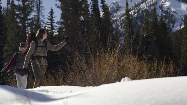 Backpackers Snowshoe Through Snow Covered Field In Utah Mountains, Man Points To Something In Distance Royalty-free stock video