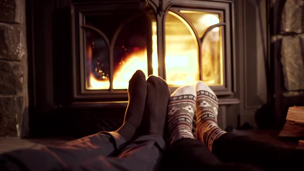 Closeup of couple's feet, warming up by cozy fire Royalty-free stock video