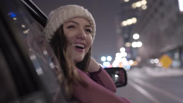 Carefree young woman leans out car window at night in downtown, she waves to people, raises her arms in the air with excitement  Royalty-free stock video