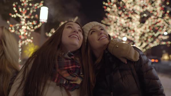 Closeup of friends walking, enjoying Christmas lights, they look up together and laugh and smile Royalty-free stock video