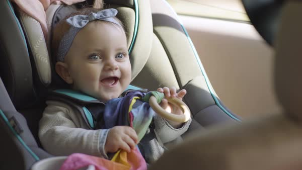 Cute baby girl plays with toy in car seat, she smiles and laughs, ready to go for a ride in family car  Royalty-free stock video