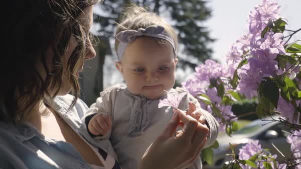 Close-up slow motion shot, mom teaches her baby girl how to smell a flower Royalty-free stock video
