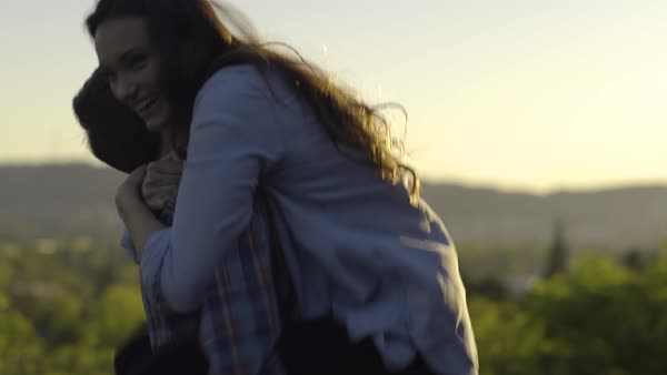 Man Holds Girlfriend In His Arms And Spins Her Around In Circle, They Laugh And Share Intimate Moment, At Sunset In Park Royalty-free stock video