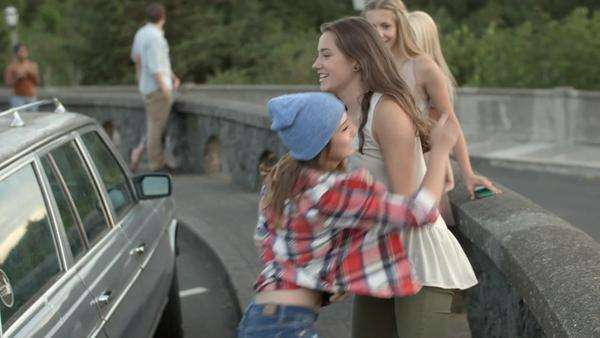 Girl helps her friend jump off of car roof, they hug and laugh Royalty-free stock video