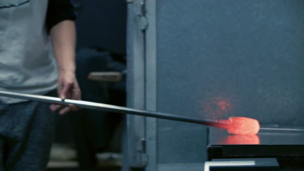 Blowing glass - rolling glass on the marver and gathering colored glass  Royalty-free stock video