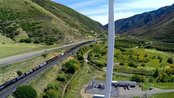 Aerial view of wind turbine with train pulling coal in the background Royalty-free stock video