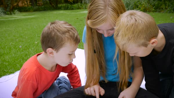 An Older Sister Shows Her Two Younger Brothers Something On A Tablet Outside In A Park