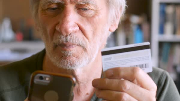 Candid moment of a smiling happy handsome mature man in 60s or 70s checking out his purchase on smart phone with debit or credit card - dolly shot Royalty-free stock video