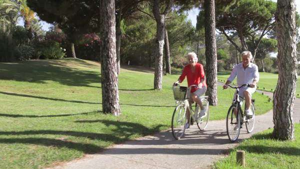 Senior couple riding bikes along path past camera position . Royalty-free stock video