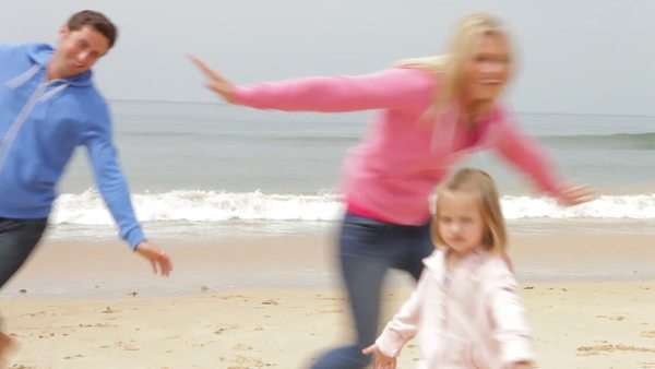 Family running up beach towards camera with arms stretched pretending to be aeroplanes. Royalty-free stock video