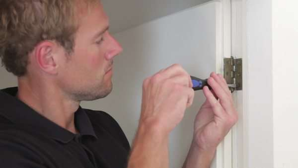 Man using screwdriver to tighten old screw on hinge. Royalty-free stock video